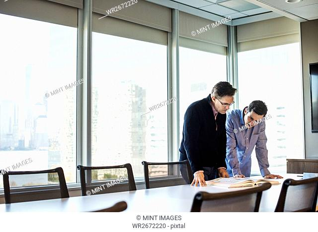 Two men standing at a table in a meeting room looking down at an open book together