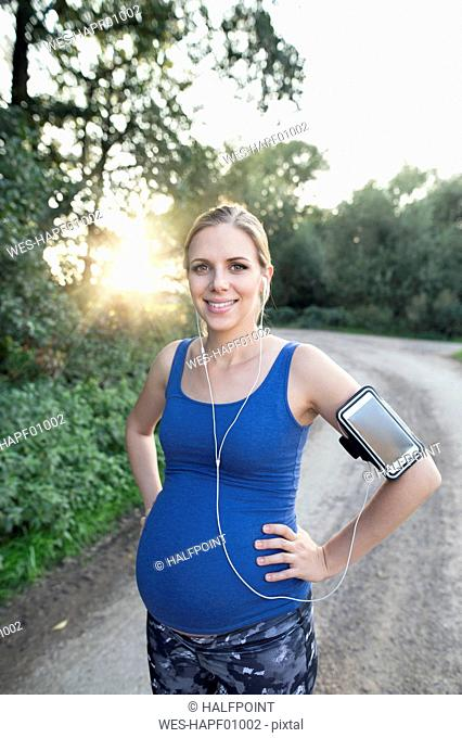 Pregnant woman smiling taking a break from jogging