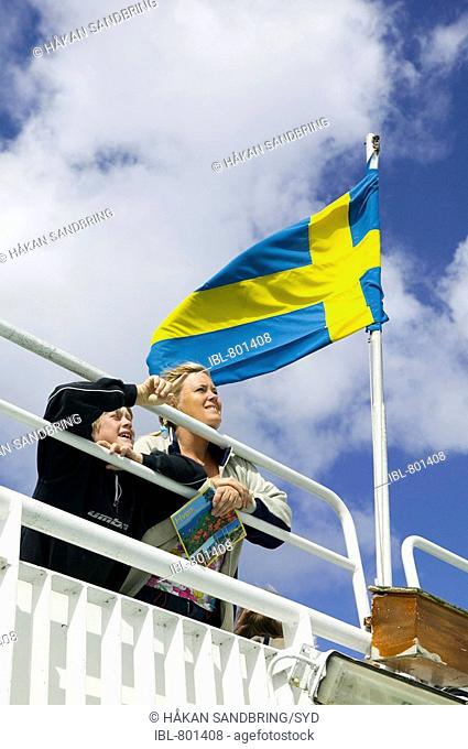 Boy and woman on a ferry, swedish flag