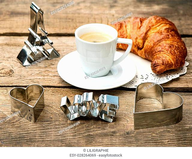 cup of coffee with croissant and heart decoration on rustic wooden background. romantic Valentine's Day breakfast with deco symbol of paris eiffel tower