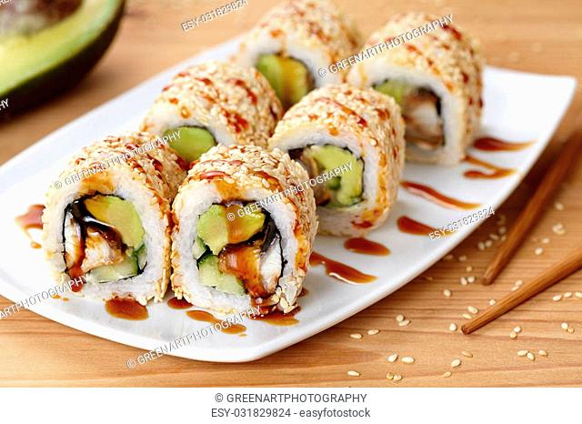 California sushi roll with eel, avocado and cucumber. Traditional Japanese rice sushi healthy seafood. White plate, wooden table background