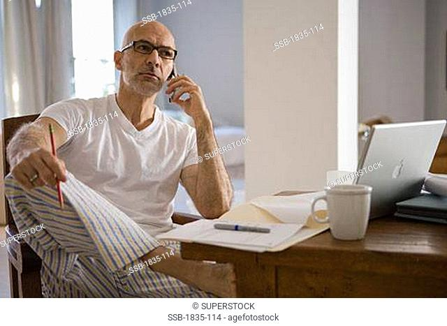 Mature man sitting at a table and talking on a mobile phone
