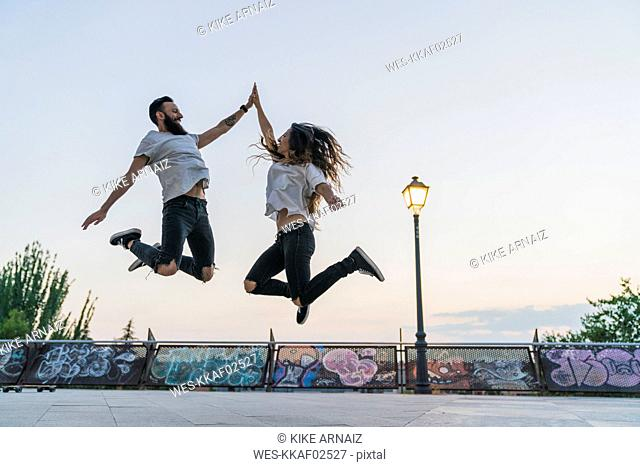 Exuberant couple jumping outdoors high fiving