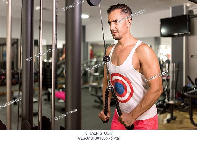 Man exercising at pull machine in gym