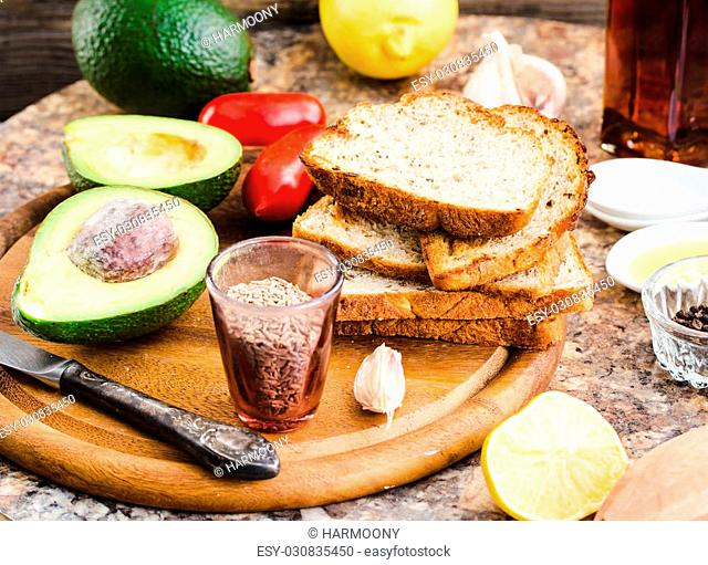 avocado halves, bread, tomatoes, a set of products for sandwiches on a wooden board,selective focus