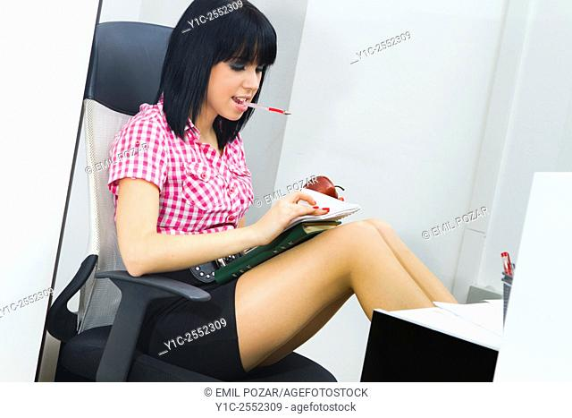 Young female secretary in office browsing papers