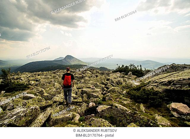 Caucasian hiker walking in rocky field in remote landscape