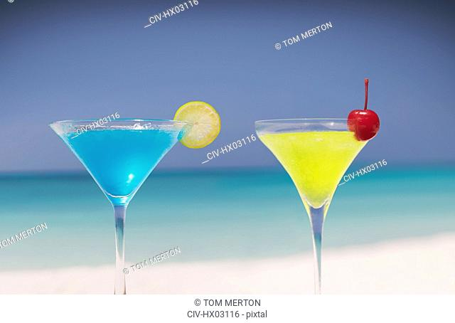 Blue and yellow cocktails in martini glasses on tropical beach