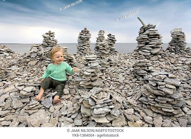 Two Years Old Kid Girl Buidling Stone Tower on Saaremaa Stony Coast, Saare County, Estonia