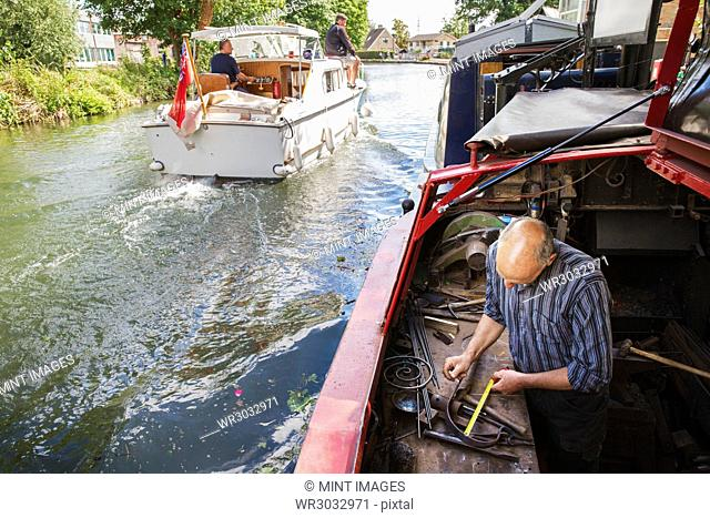High angle view of a blacksmith working at his bench on a narrowboat on the water, holding a tape measure. A motorboat underway