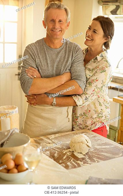 Smiling affectionate couple hugging, baking in kitchen