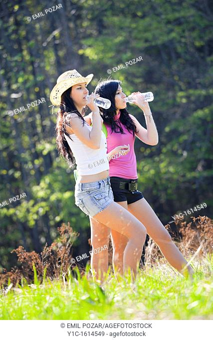 Two girls are drinking water walking uphill