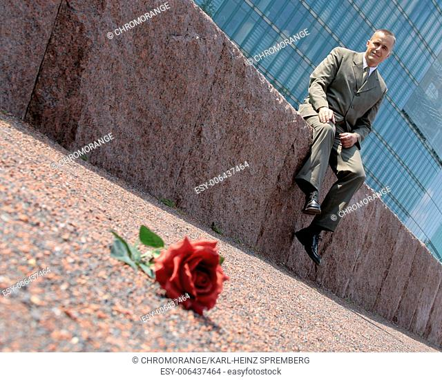 Rose lying on the Floor, Man sitting on Wall