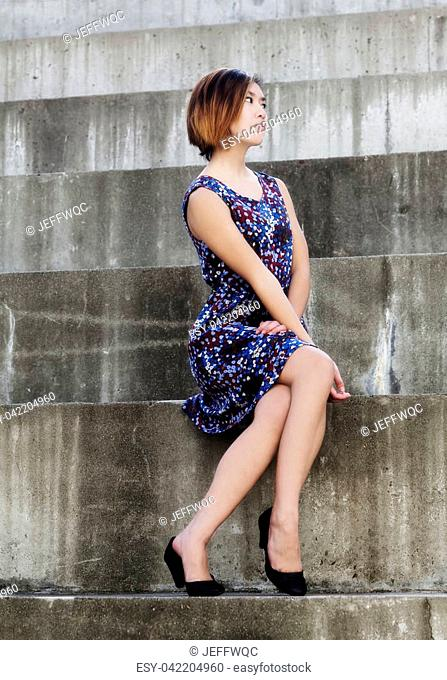 Attractive Slim Asian American Woman Sitting In Dress Outdoors On Large Cement Steps Looking To the Side