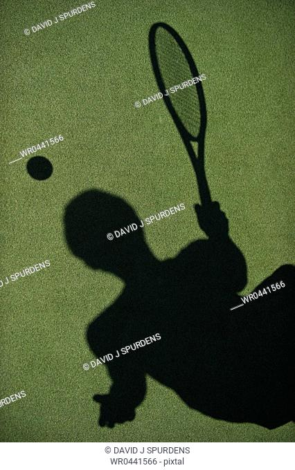 The sillhouette of a tennis player on court