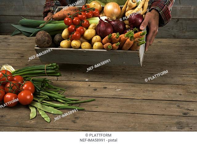 A man holding a box containing fresh vegetables Sweden