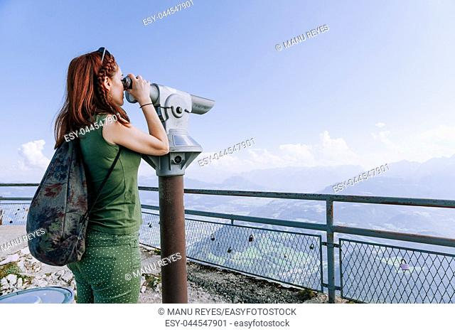 Young redhead woman viewing the mountains and sunset in Coin Operated Binocular viewer traveler. Untersberg, Salzburgo, Austria