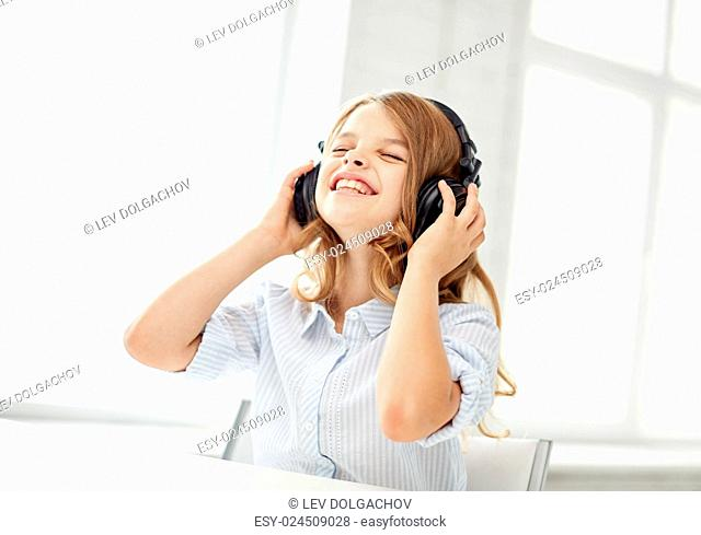 people, children, leisure, technology and music concept - smiling little girl with headphones at home