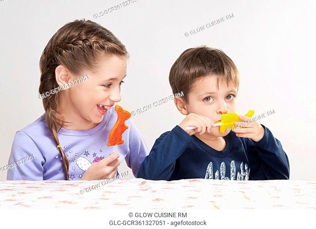 Boy and his sister holding candies