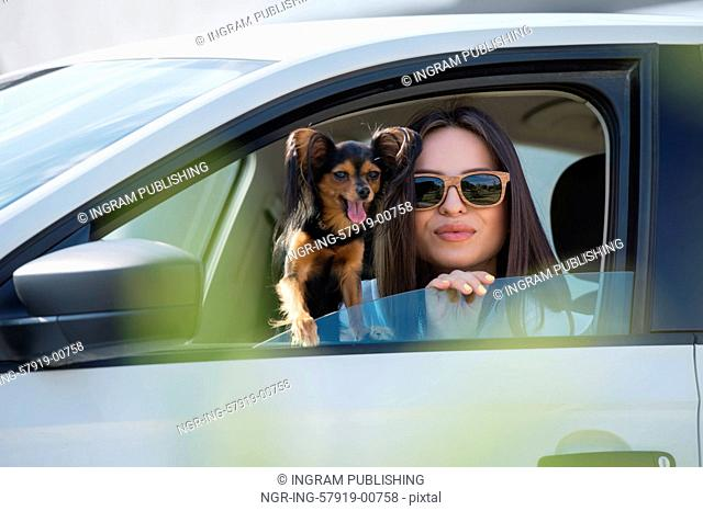 Woman and dog in car on summer travel. Funny dog traveling. Vacation with pet concept