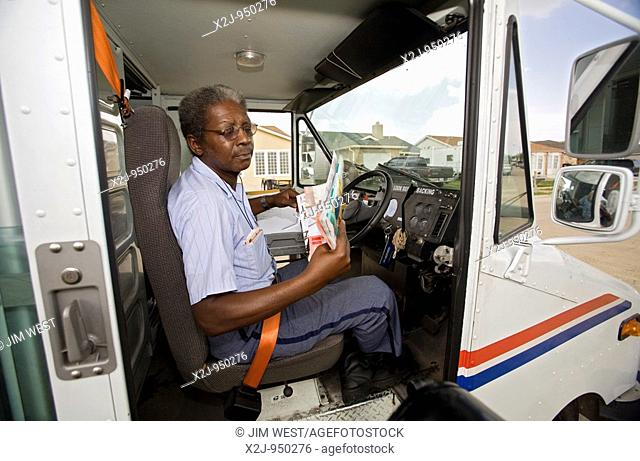 New Orleans, Louisiana - Letter carrier Kevin Miller delivers mail to a FEMA trailer parked on the lawn of a home in New Orleans East