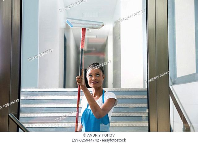 African Woman Cleaning Glass With Rubber Window Cleaner
