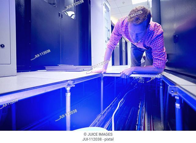 Technician checking cabling under floor of data centre server room