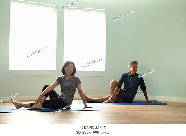 Mature couple sitting on yoga mat leaning on hand, legs crossed looking away smiling