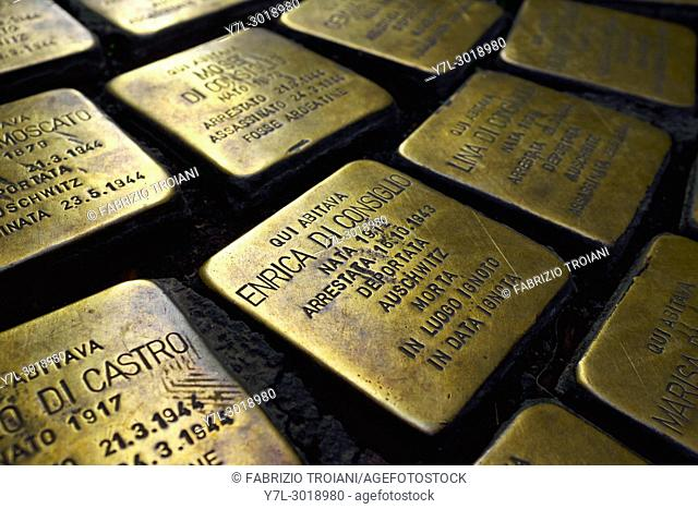 cobblestone-size concrete cube bearing a Stolperstein,a brass plate inscribed with the name and life dates of victims of Nazi extermination or persecution