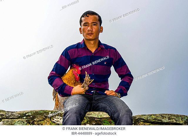Local man sitting with a rooster, soon to be sacrificed at the Khadga Devi Mandir Temple, Darsain Hindu Festival, Bandipur, Tanahun, Nepall