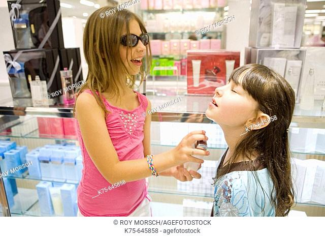 young girls testing perfume at cosmetic counter