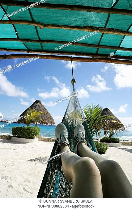 A woman relaxing in a hammock on Island Cozumel, Caribbean