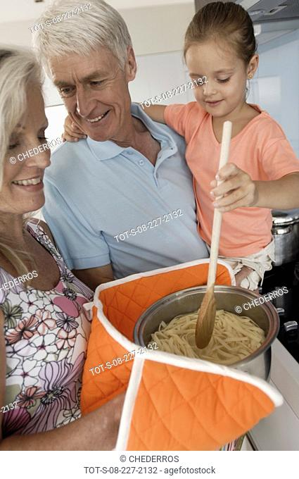 Senior couple with their granddaughter preparing food in the kitchen
