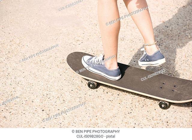 Legs of young female skateboarder skateboarding