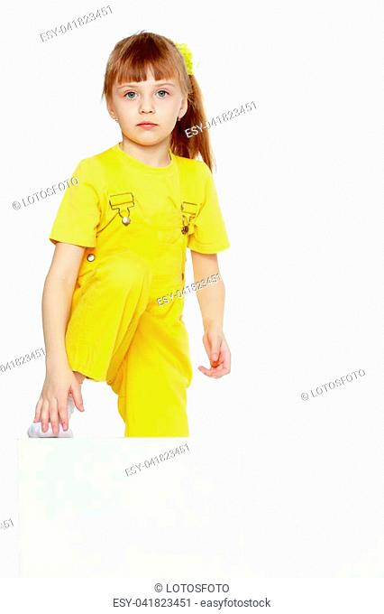 Girl with a short bangs on her head and bright yellow overalls.She put her foot on the white advertising banner