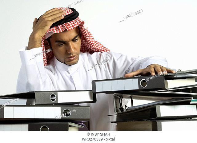 Young Arab man sitting with a lot of files