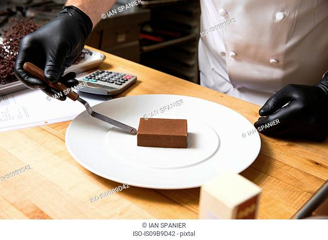 Cropped view of chef placing cake on plate