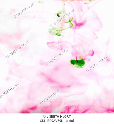 Abstract of pink and green ink dispersing in water