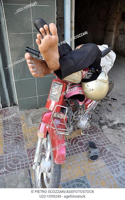 Phnom Penh (Cambodia): man sleeping on a motor-bike