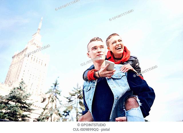 Young man giving laughing girlfriend a piggy back in city