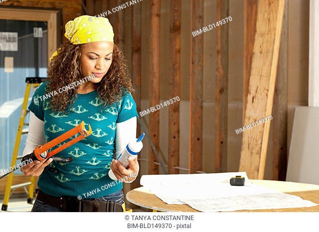 Hispanic woman holding caulking gun