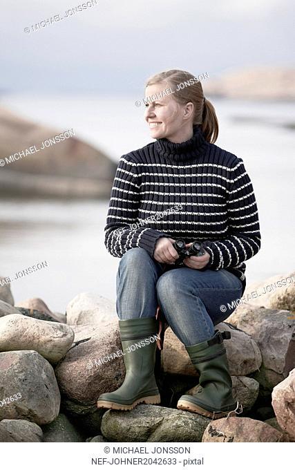 Woman with binoculars at sea