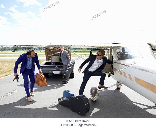 Three musicians transferring from car to plane; Langley, British Columbia, Canada