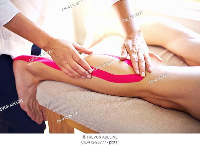Physical therapist applying kinesiology tape to man's leg