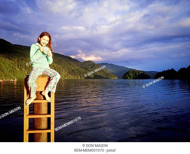Mixed race girl sitting on piling next to lake