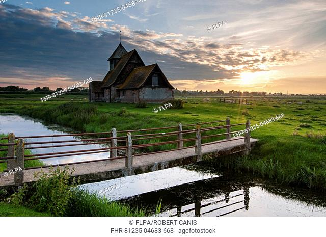 View of grazing marsh with footbridge across flooded ditch and church at sunset, St. Thomas a Becket Church, Fairfield, Walland Marsh, Romney Marsh, Kent