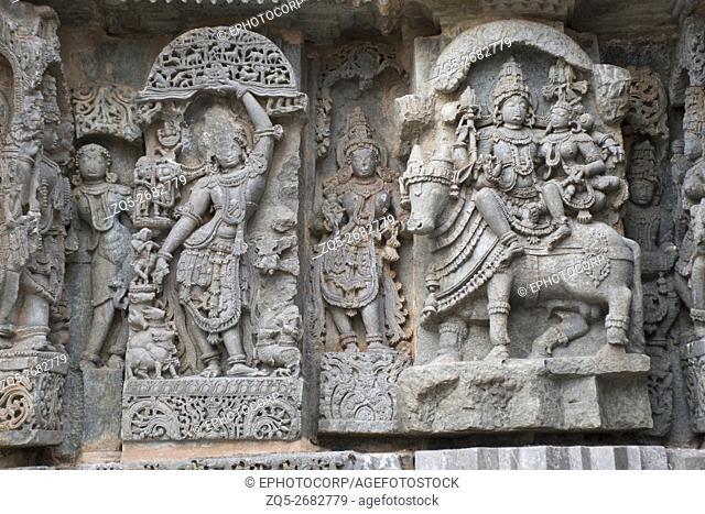 Ornate wall panel reliefs depicting (From left) Krishna as Govardhan Giridhari and Shiva-Parvati seated on Nandi, Kedareshwara temple, Halebidu, Karnataka