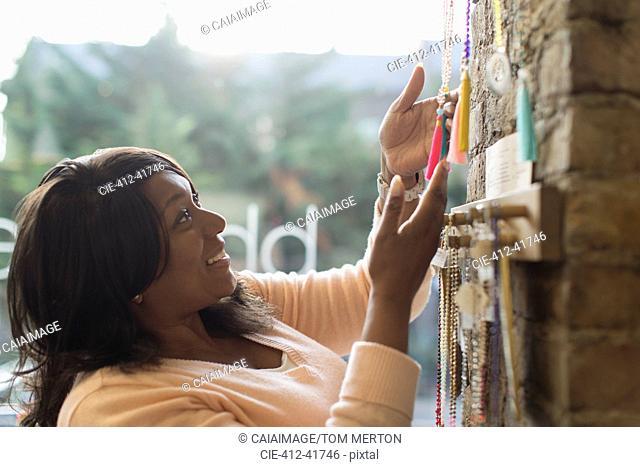Woman browsing mala beads in shop