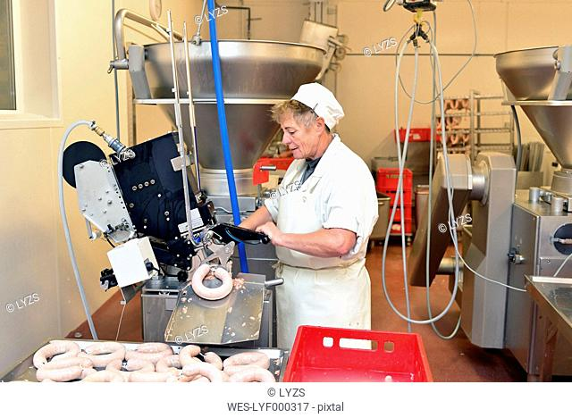 Woman working at sausage production in a butchery