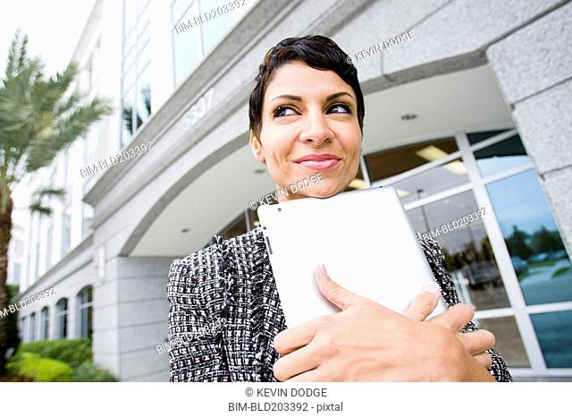 Cape Verdean businesswoman holding tablet computer outdoors